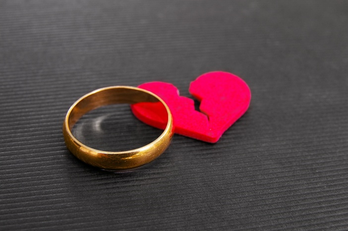 gold wedding ring and red broken heart ( divorce concept )